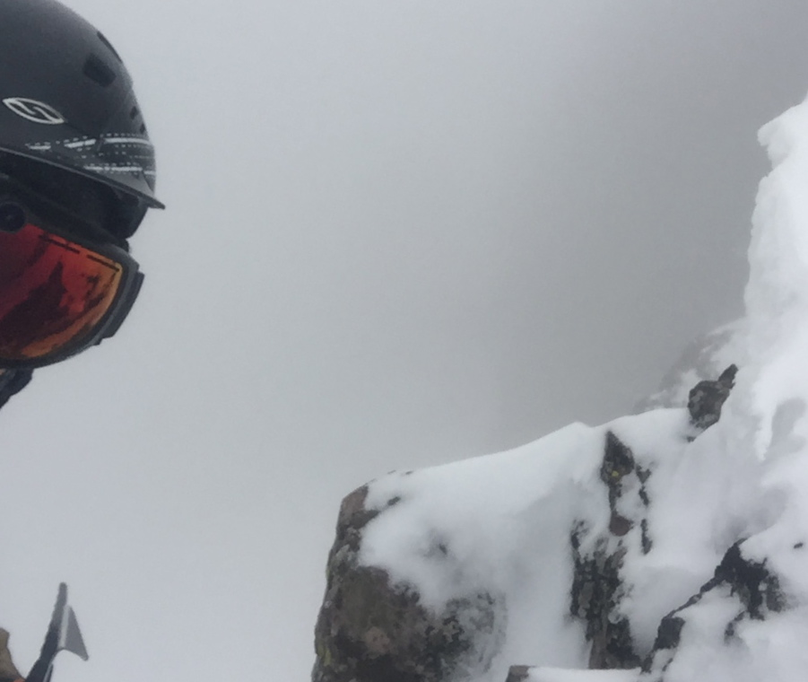A foggy selfie tucked out of the wind next to the summit block.